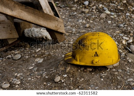 Dirty old work helmet left on the ground of construction site - stock photo