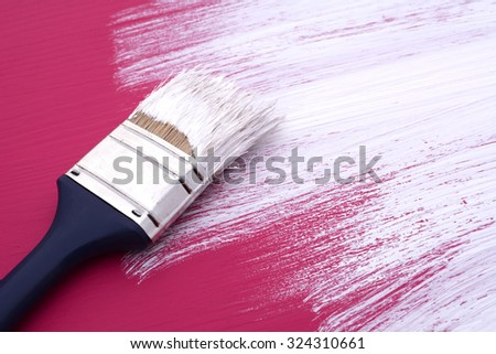 Dirty paintbrush with white paint rests on half-painted board, previously painted pink - stock photo