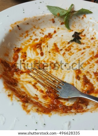 Dirty plate, empty dish with remaining spaghetti sauce and fork