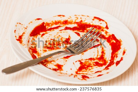 Dirty plate on the table. Tomato sauce smeared on a plate. - stock photo