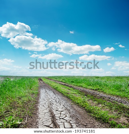 dirty road close up to horizon in cloudy sky - stock photo