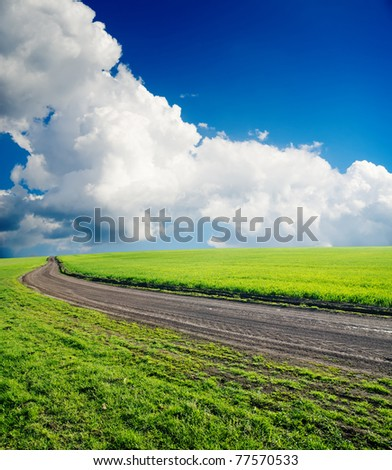 dirty road in green field under cloudy sky - stock photo