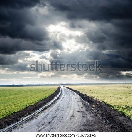 dirty road to cloudy horizon. rain before - stock photo