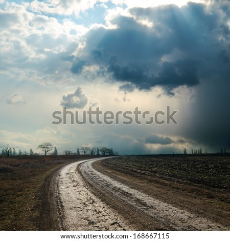 dirty road to dramatic sky - stock photo