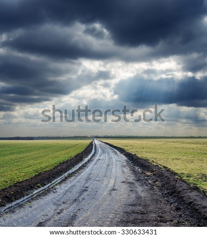 dirty road to horizon and dramatic sky. rain before - stock photo