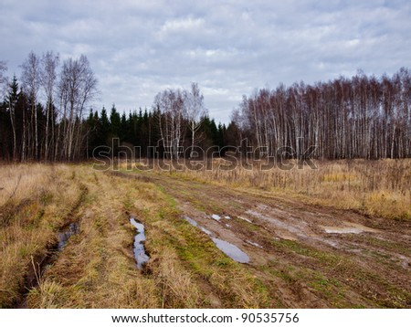 Dirty road with mud and pulldles over field in Russia. - stock photo