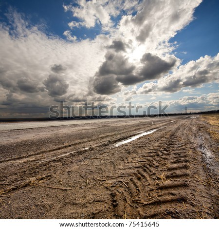 Dirty rural road and cloudy blue sky - stock photo