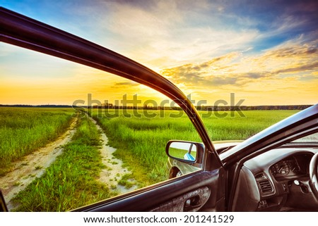 Dirty rural road in field, meadow, countryside. View from car window. Freedom and dream concept - stock photo