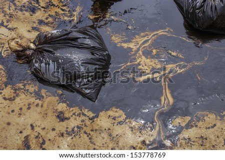 Dirty Sand beach with Plastic bags which contain crude oil from the clean up operation on oil spill accident on Ao Prao Beach at Samet island on July 2013 in Rayong, Thailand. - stock photo