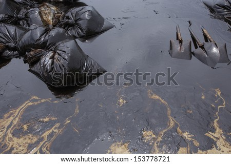 Dirty Sand beach with Spades and Plastic bags which contain crude oil from the clean up operation on oil spill accident on Ao Prao Beach at Samet island on July 2013 in Rayong, Thailand. - stock photo