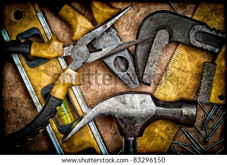 Dirty set of hand tools on a wooden panel - stock photo