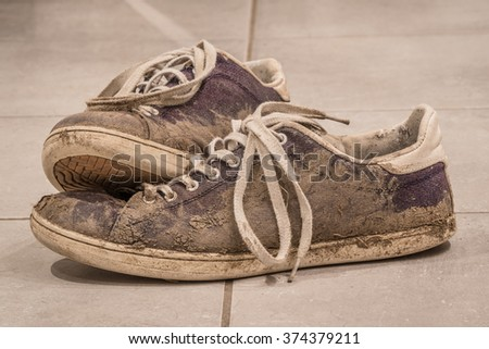 Dirty shoes with mud and soil on a floor - stock photo
