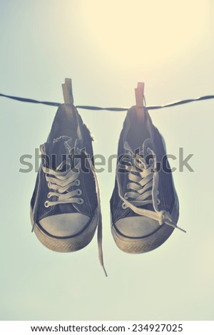Dirty Sneakers hanging on the clothesline.  - stock photo