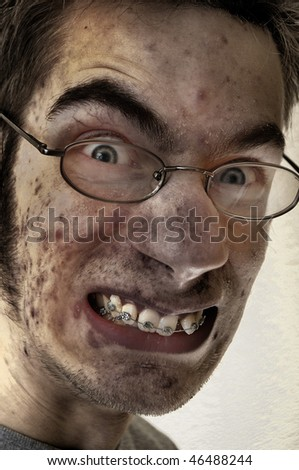 Dirty Soot and ash cover a man's face. He is gritting his teeth in agony. - stock photo