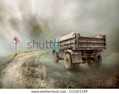 Dirty truck on a country road and cloudy sky - stock photo