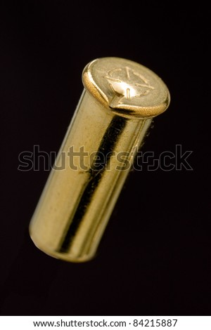 Dirty Used .22 LR shell casing on black - stock photo