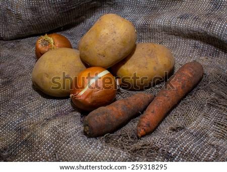 Dirty vegetables on burlap - stock photo