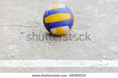 Dirty volleyball near the white line of field
