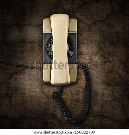 dirty wall and old telephone - stock photo