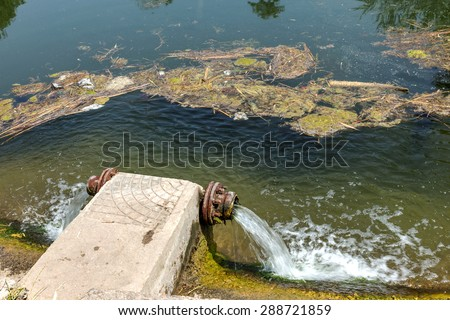 Dirty waste water from rusted culvert large flow merge into the city pond, pollute the water. Bathing is prohibited. Dirty water. Dangerous bacteriological situation. Garbage in the water reservoir - stock photo