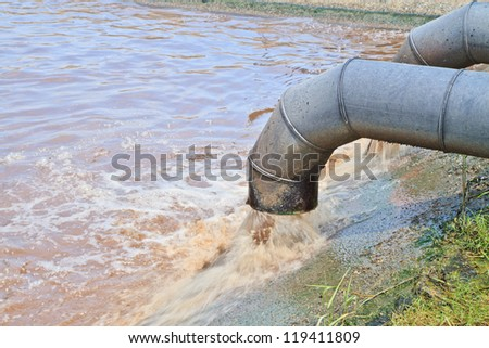 Dirty water flows from a pipe. Toxic production wastes - stock photo