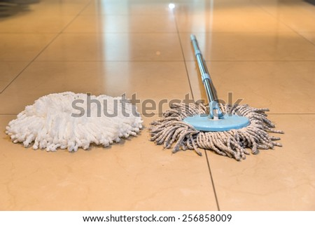 Dirty wet mop with a new clean string alongside on a tiled kitchen floor head in a healthcare, hygiene and household cleaning concept - stock photo