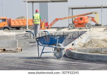 Dirty wheelbarrow standing at construction site, construction worker and machines in background - stock photo