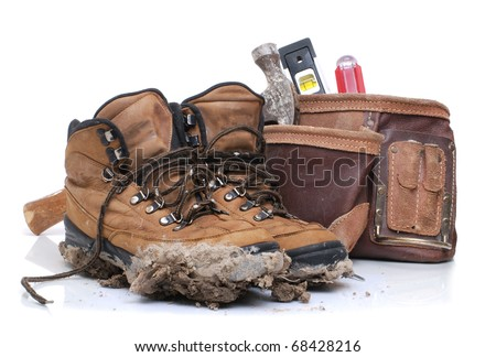 dirty work boots and tool belt - stock photo