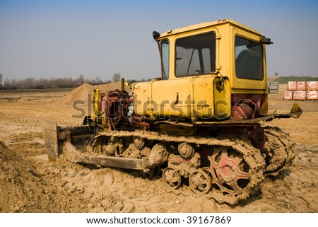 Dirty yellow bulldozer on construction site