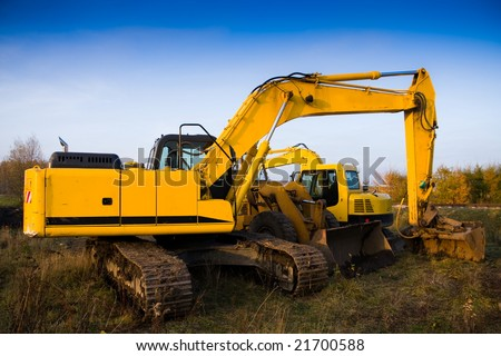 Dirty yellow excavator and bulldozer over blue sky
