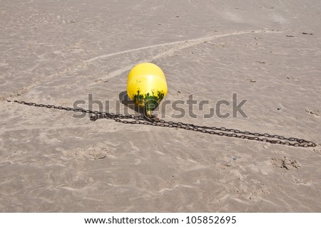 Dirty yellow safety buoy at the beach - stock photo