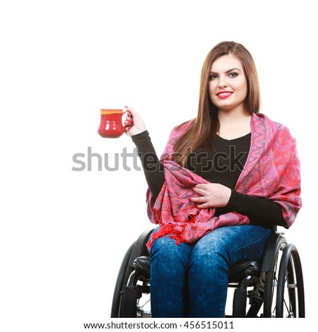 Disability drink relax leisure concept. Cheerful crippled lady on wheelchair. Smiling disabled girl holding red cup drinking beverage. - stock photo