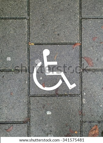 Disability or wheel chair symbol on the brick floor - stock photo