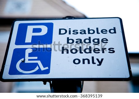 Disable badge holder parking road sign - stock photo