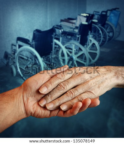 Disabled and Handicapped elderly medical health care concept with a young person holding and giving a helping hand to an old elderly grandparent with a group of wheelchairs in the background. - stock photo