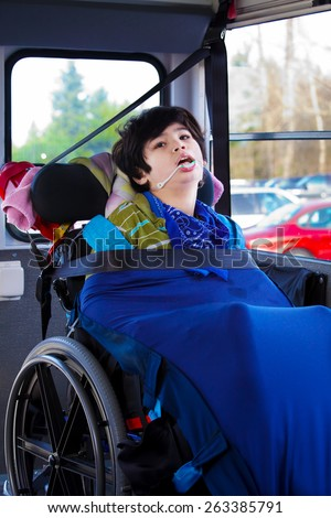Disabled biracial eight year old boy in wheelchair buckled with seatbelt on school bus - stock photo