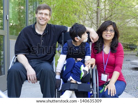 Disabled biracial six year old boy in wheelchair with parents outdoors - stock photo