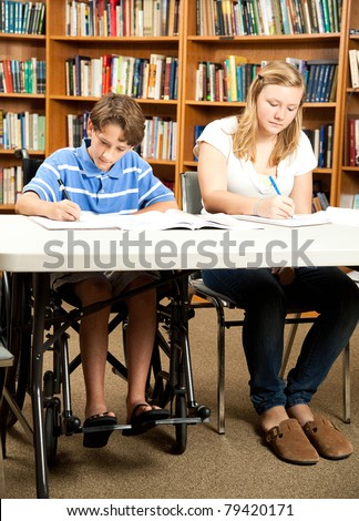 Disabled boy and a friend doing homework in the school library. - stock photo