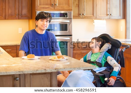 Disabled boy in wheelchair in kitchen with older brother, ready to have lunch of hamburger and french fries
