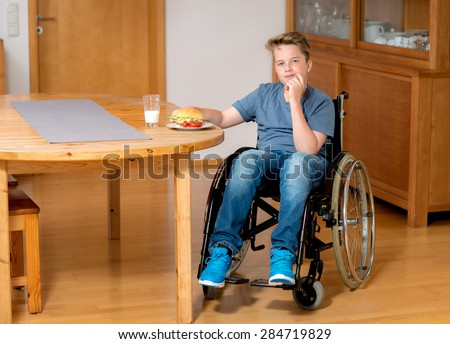 disabled boy in wheelchair is eating in the living room - stock photo