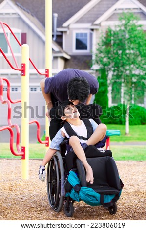 Disabled boy in wheelchair with big brother at park - stock photo