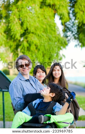 Disabled boy in wheelchair with family outdoors on sunny day sitting at a park - stock photo