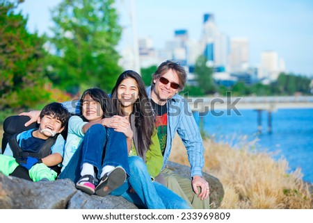 Disabled boy in wheelchair with family outdoors on sunny day, with city skyline in background - stock photo