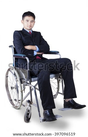 Disabled businessman wearing formal suit while sitting on wheelchair and looks confident, isolated on white background - stock photo