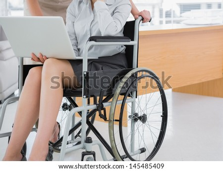Disabled businesswoman showing laptop to colleague in an office - stock photo