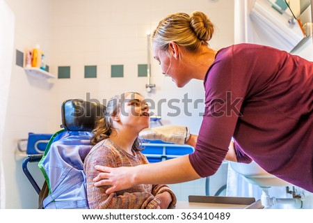 Disabled child in a wheelchair being cared for by a special needs care assistant/ Working with disability - stock photo