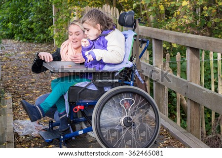 Disabled child in a wheelchair relaxing outside with a carer / Working with disability - stock photo