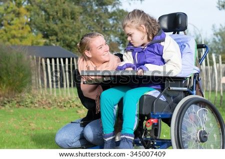Disabled child in a wheelchair relaxing outside with help from a care assistant / Working with disability