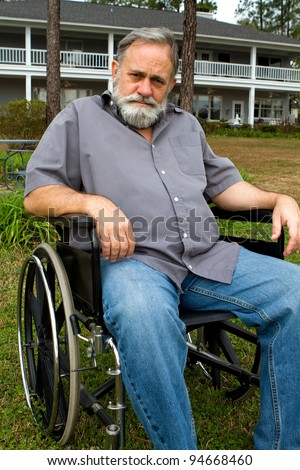 Disabled crippled man sits in his wheelchair in front of his home in the grass. - stock photo