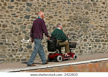 Disabled elderly man riding a mobility vehicle on an uphill path, with another elderly man walking behind. - stock photo